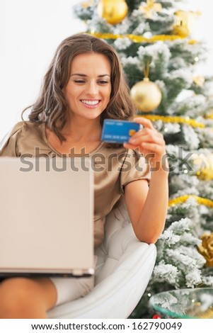 Portrait of happy young woman with credit card using laptop near christmas tree - stock photo