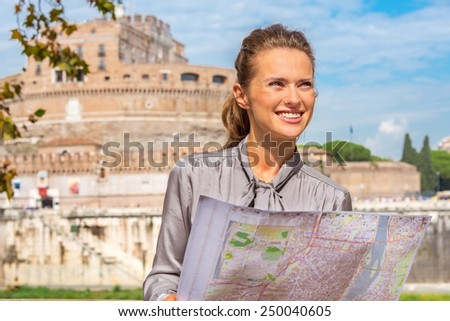 Portrait of happy young woman with map on embankment near castel sant'angelo in rome italy - stock photo