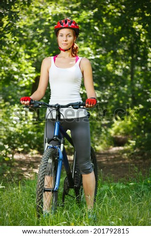 Portrait of happy young woman with mountain bike outdoors. - stock photo