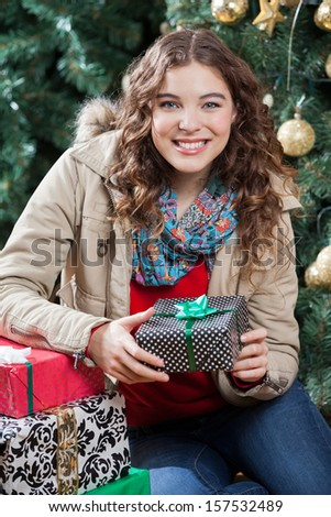 Portrait of happy young woman with presents sitting against Christmas tree in store - stock photo