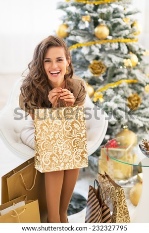 Portrait of happy young woman with shopping bags near christmas tree - stock photo