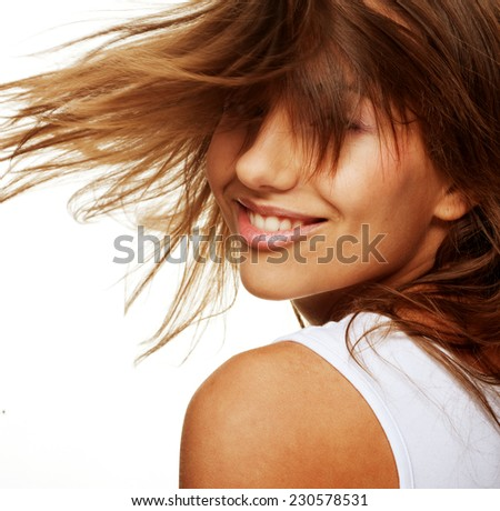 Portrait of happy young woman with wind in hair - stock photo