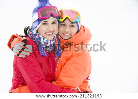 Portrait of happy young women in warm clothing embracing outdoors - stock photo