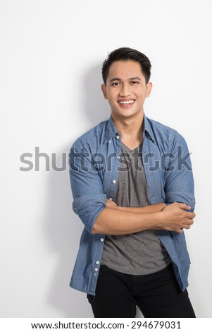 Portrait of Hapy young asian man posing on the white background, crossed arms