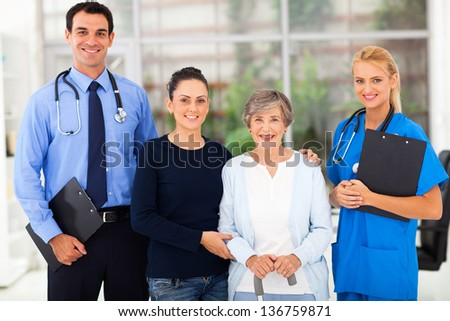 portrait of health workers standing with senior patient and her daughter - stock photo