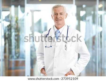 Portrait of healthcare worker. Image of senior male doctor wearing lab coat and standing at private clinic while looking at camera and smiling.  - stock photo