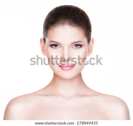 Portrait of healthy beautiful woman with cosmetic cream under the eyes - isolated on white. - stock photo