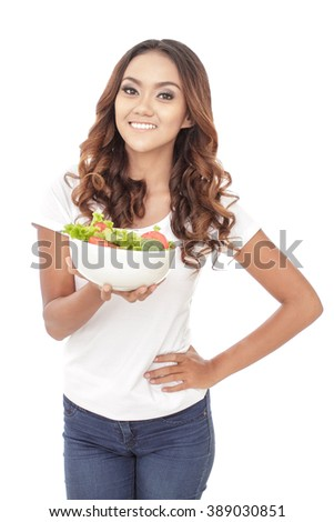 portrait of healthy casual woman holding a bowl of salad isolated on white background