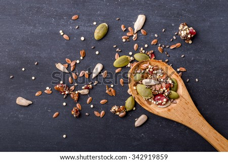 portrait of healthy cereal grains on wooden spoon with black board for background - stock photo