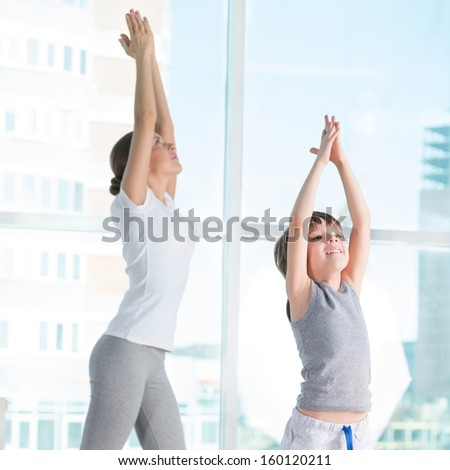 Portrait of healthy female and her son practicing physical exercise at gym