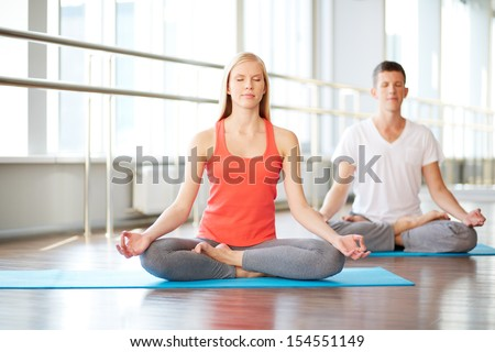 Portrait of healthy girl and guy doing exercise for relaxation in gym - stock photo