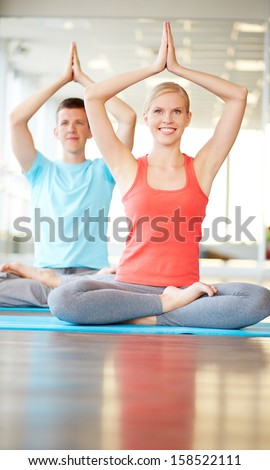 Portrait of healthy girl and guy meditating in gym - stock photo