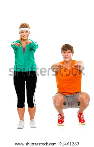 Portrait of healthy girl and man in sportswear sitting on squat isolated on white - stock photo