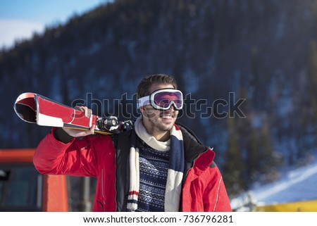 Portrait of healthy man with pair of skis in hands looking aside and smiling