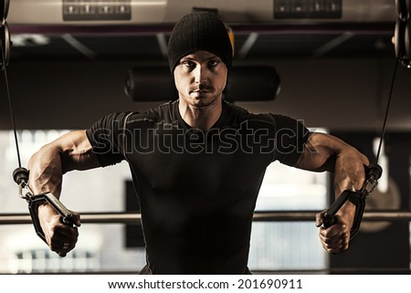 Portrait of healthy muscular man exercising at gym - stock photo