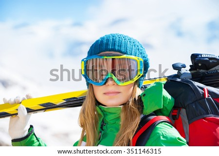 Portrait of healthy woman wearing sportive mask and holding ski in hands, spending winter holidays in snowy mountains - stock photo