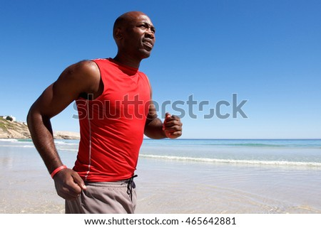 Portrait of healthy young african guy running along the seashore
