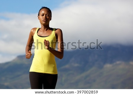Portrait of healthy young black woman running outdoors in nature