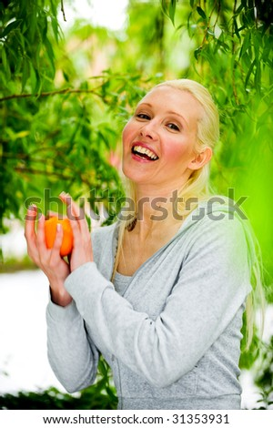 Portrait of healthy young blond woman catching an orange in an outdoor location