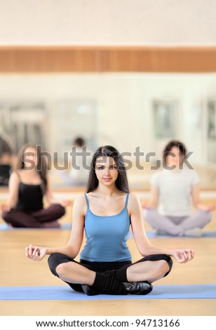 Portrait of healthy young woman practicing yoga on exercising mat - stock photo