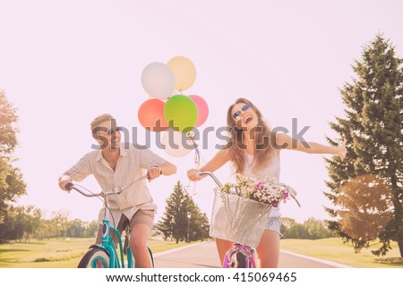 Portrait of heerful young woman and her boyfriend having walk with bicycles - stock photo