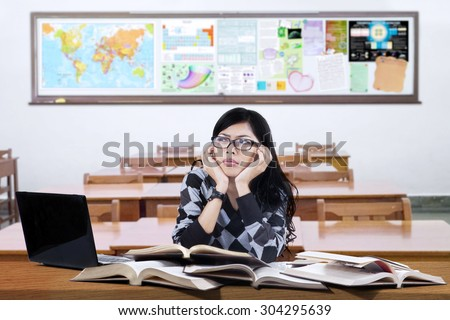 Portrait of high school student sitting in the classroom while studying and thinking idea - stock photo