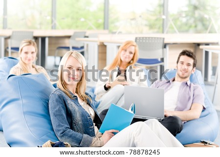 Portrait of high-school study group with laptop sitting together