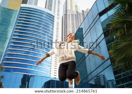 portrait of hipanic businesswoman jumping mid air for joy near office buildings and skyscraper. Full lenght, low angle - stock photo