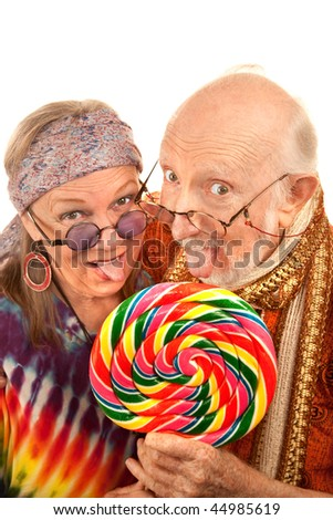 Portrait of hippie seniors licking a large lollipop - stock photo