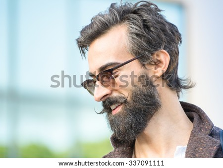 Portrait of hipster guy with confident face expression - Autumn fashion male model posing outdoors - Young man with beard and alternative mustache - Soft retro filter and shallow depth of field - stock photo