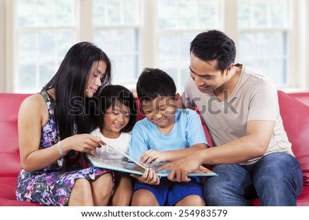 Portrait of hispanic family enjoy read a story book together at home - stock photo
