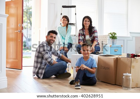 Portrait Of Hispanic Family Moving Into New Home - stock photo
