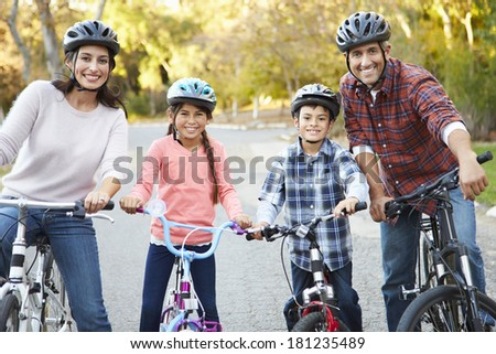 Portrait Of Hispanic Family On Cycle Ride In Countryside - stock photo