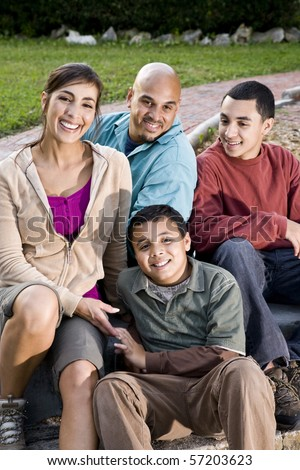Portrait of Hispanic family with two boys outdoors - stock photo