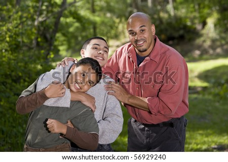 Portrait of Hispanic father and two boys outdoors in outdoor park - stock photo