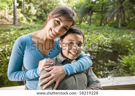 Portrait of Hispanic mother and 10 year old son outdoors in park - stock photo