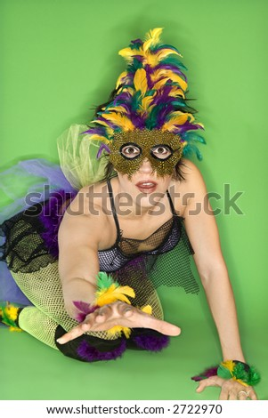 Portrait of Hispanic woman in Mardi Gras type costume and mask kneeling on floor with hand reaching out against green background. - stock photo