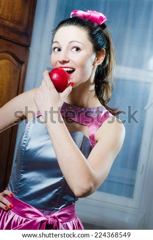portrait of holding red juicy apple beautiful funny pinup young lady happy smiling and looking at camera on the window copy space background - stock photo