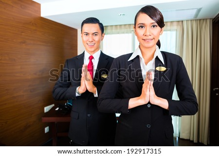 Portrait of hotel staff greeting with hands put together - stock photo