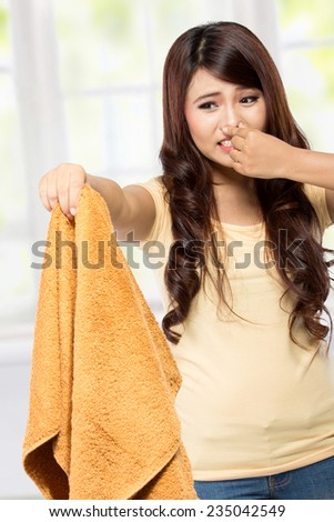 portrait of housewife holding a bad smell laundry - stock photo