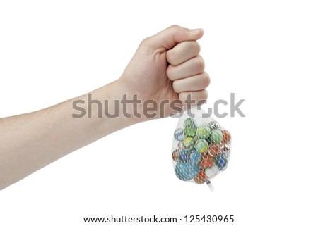 Portrait of human hand holding net bag of marbles against white background - stock photo