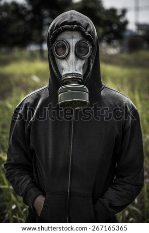 Portrait of human wearing hoodie and gas-mask - stock photo