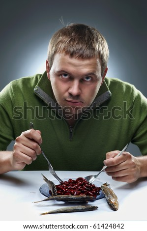 Portrait of hungry man. Eating beans and fish. - stock photo