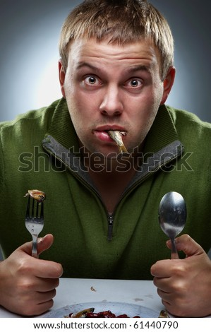 Portrait of hungry with fish in mouth - stock photo