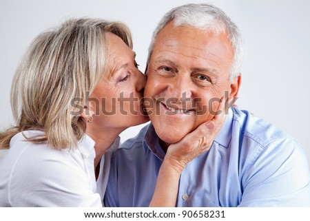 Portrait of husband being kissed by his loving wife - stock photo