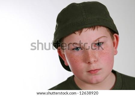 portrait of husky boy with freckles in hat - stock photo