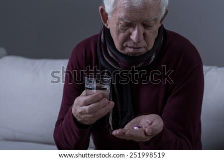 Portrait of ill senior man taking medicament - stock photo
