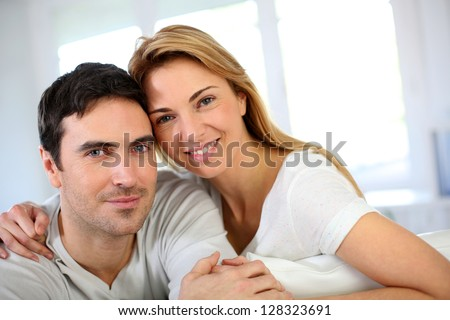 Portrait of in love couple sitting in sofa - stock photo