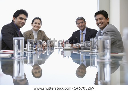 Portrait of Indian business people sitting at conference table - stock photo