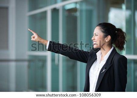 Portrait of Indian business woman pointing with her arm out stretched.